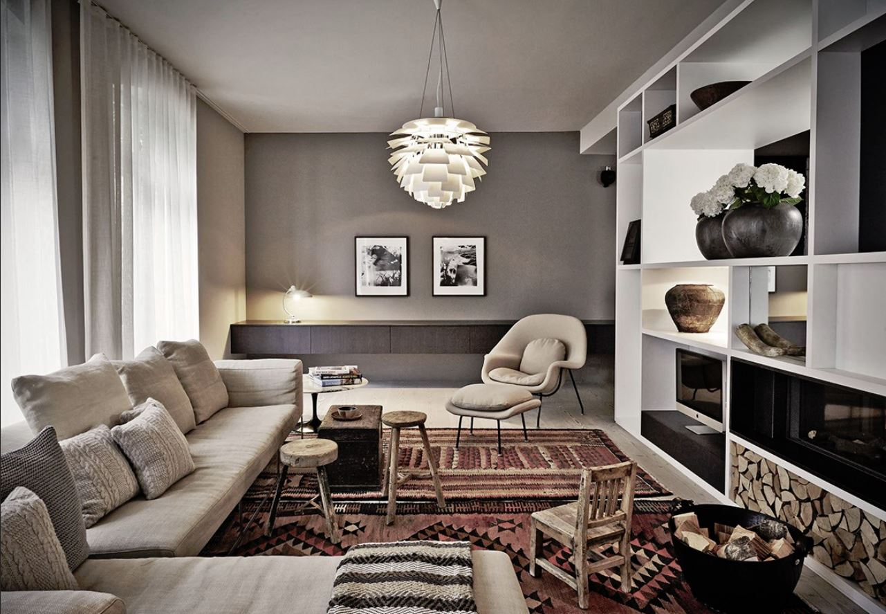 Датский интерьер: диван на высоких ножках, светлая отделка, удобное кресло