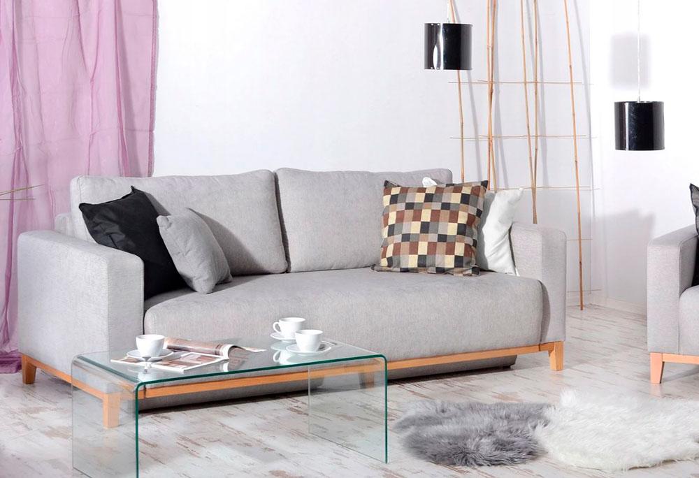 Серый диван в интерьере светлой квартиры, стеклянный журнальный столик, декоративные шкуры на светлом полу