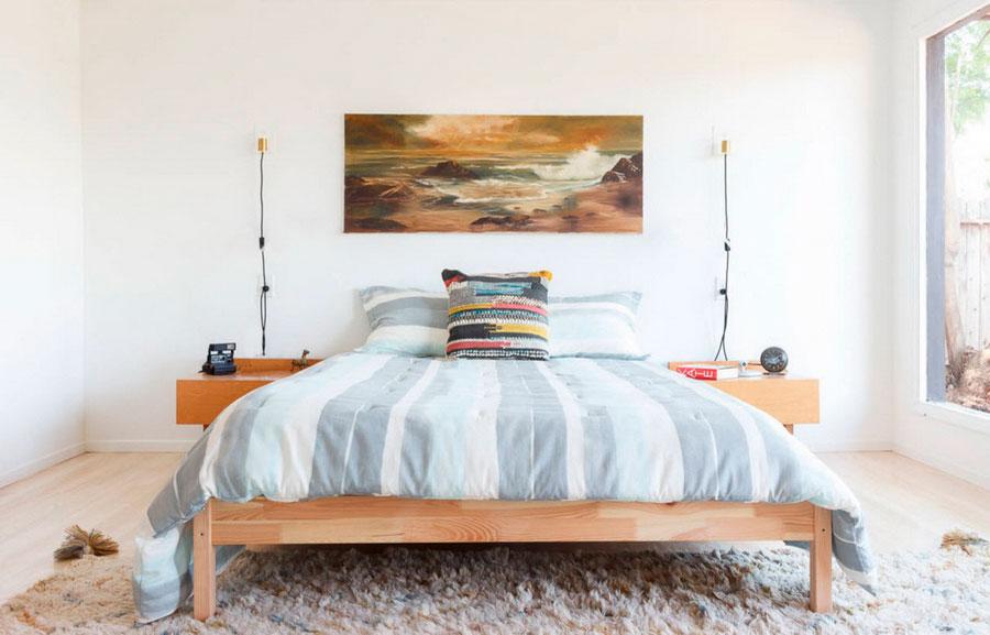 Деревянная кровать, текстиль с голубыми полосами, поглощающая внимание картина на стене, ковёр с высоким ворсом для комфорта и уюта