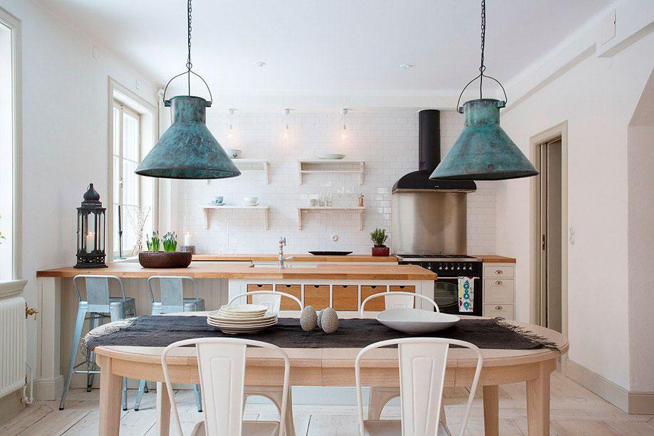 Люстра Лофт в скандинавском стиле интерьера. Сочетание стиля Лофт и Скандинавского. Деревянные столы и стулья, кухонная поверхность. Состаренные плафоны люстр, светлый потолок и стены