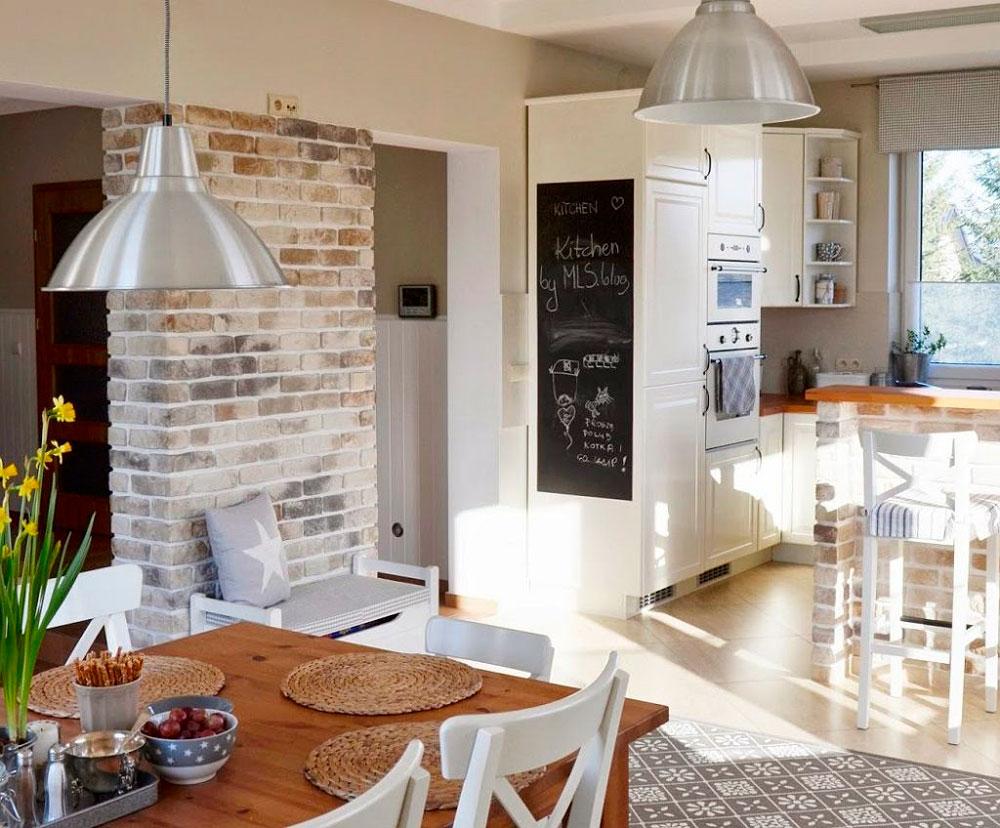 Оформленная кухня в скандинавском стиле: кирпичная стена, широкий плафон люстры, деревянный стол, белые стулья, на полу плитка пэчворк