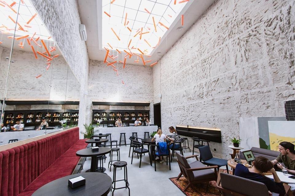 Фото интерьера ресторана с белыми стенами с оригинальной лепниной, стеклянным потолком и зеркалами на стенах