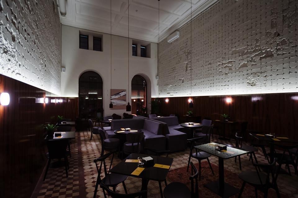 Фото интерьера ресторана с высокими 7-ми метровыми потолками, кафельной плиткой, мягкими диванами и небольшими квадратными столиками