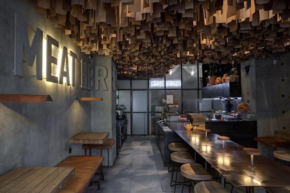 Фото гостевого зала ресторана с серыми стенами и полом, массивным баром и необычным потолком с тонкими деревянными пластинами различной длины