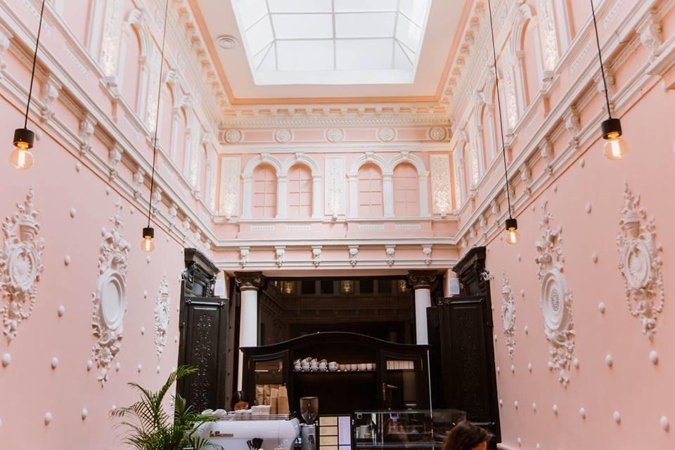 Фото интерьера ресторана с нежно-розовыми стенами и белой лепниной высотой 7 метров