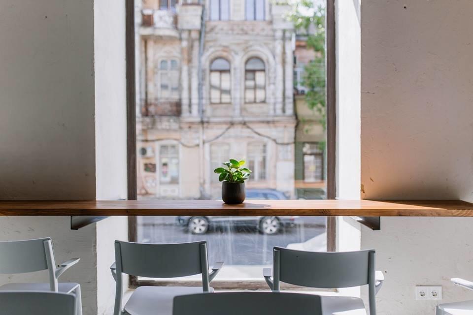 Фото высокой деревянной барной стойки с белыми стульями на фоне панорамного окна