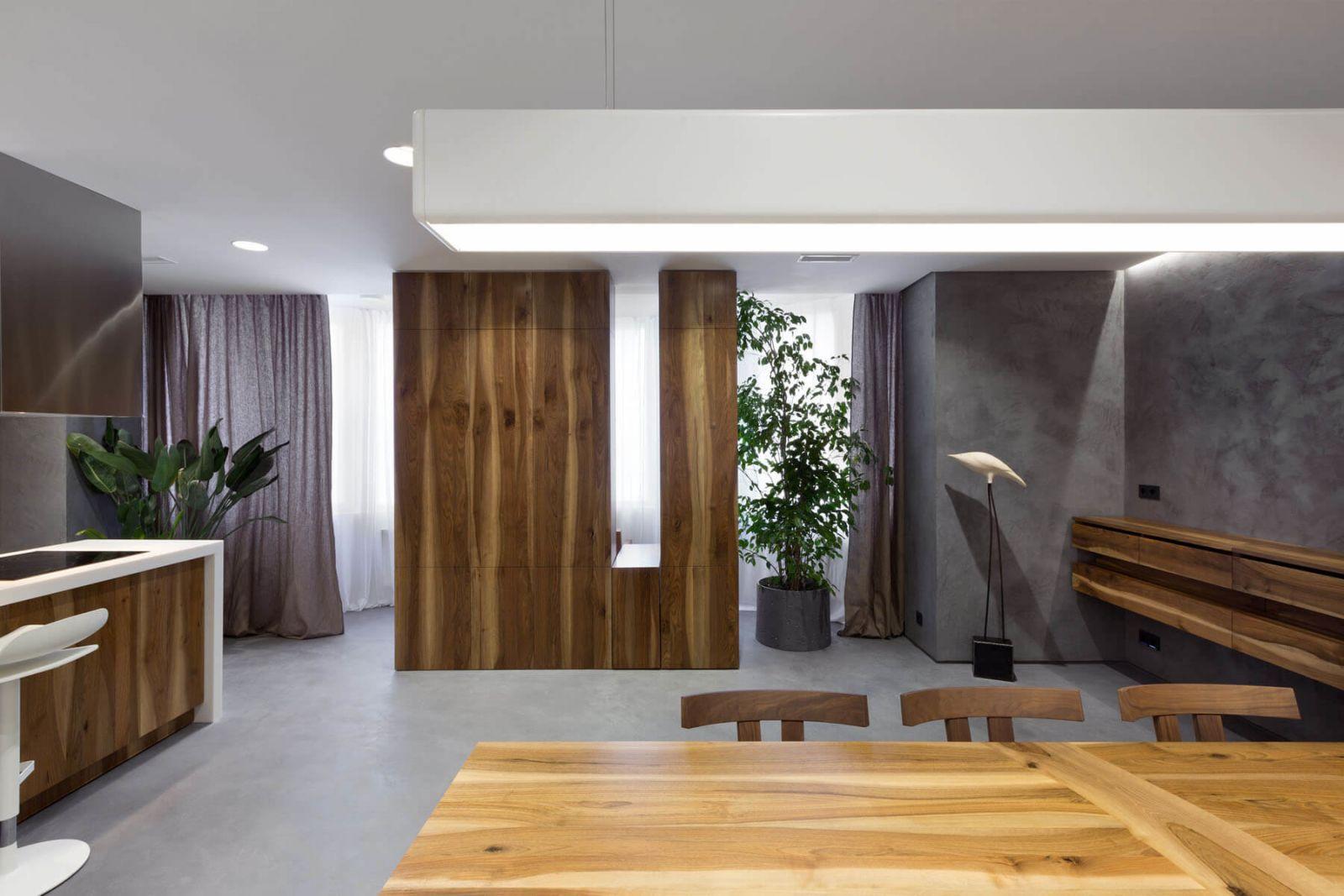 Массив дерева теплых природных оттенков, присутствующий в отделке всех помещений квартиры контрастирует с холодным серым полом и стенами, создавая атмосферу домашнего уюта