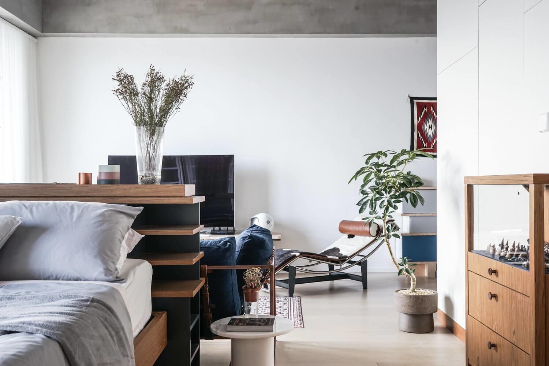 Спальное место идеально вписано в общее пространство, отделенное от гостиной с помощью удобной перегородки
