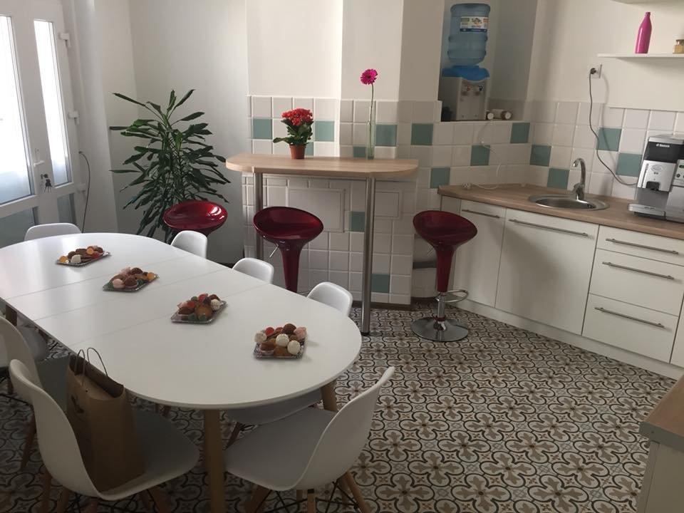 Фото интерьера кухни библиотеки с белым овальным столом, белыми стульями и барной стойкой
