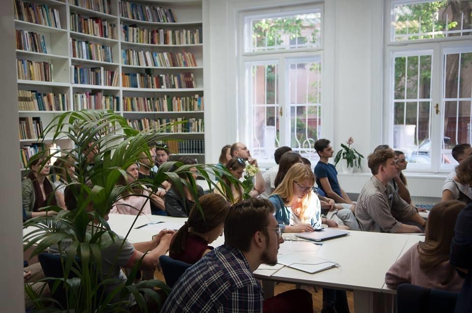 Фото людей сидящих за столом в окружении книжных стеллажей