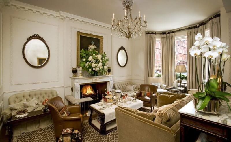 Тепло и уют строгому английскому стилю добавляет камин с аристократичными деталямиинтерьера и живыми цветами