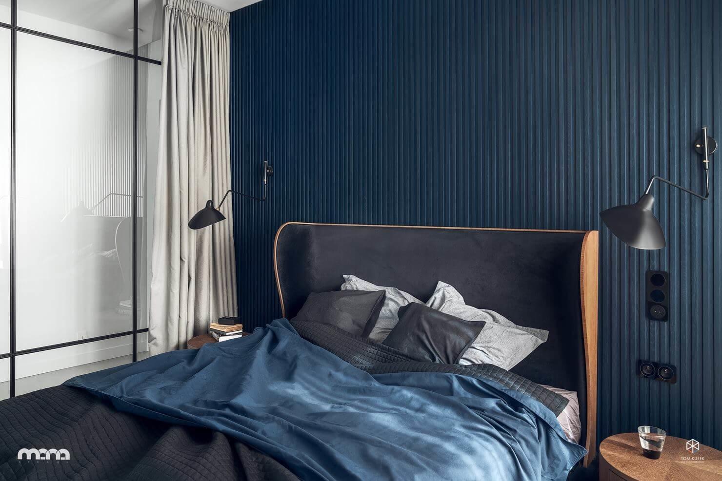В спальне ограничились минимум мебели, сделав акцент на кровать с завышенным изголовьем мягких закругленных форм, которые также напоминают о стилистике 1950-х годов в современном прочтении