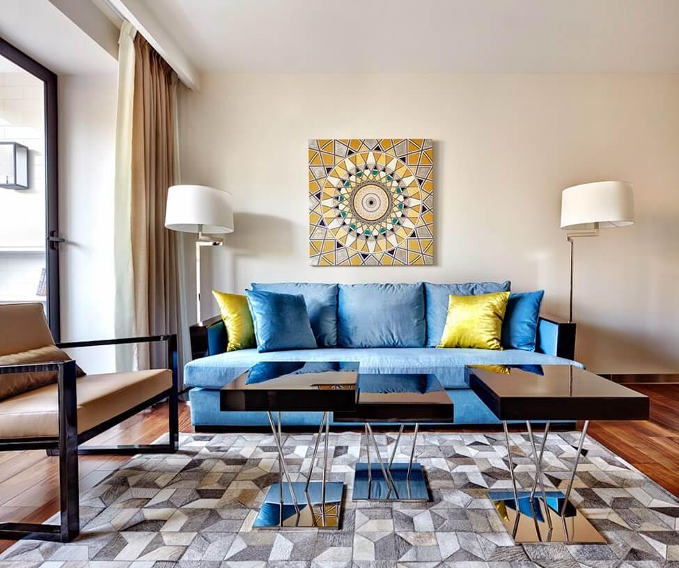 Геометрическое солнце на картине, оттеняемое желтыми диванными подушками,добавляет яркости пастельному оформлению