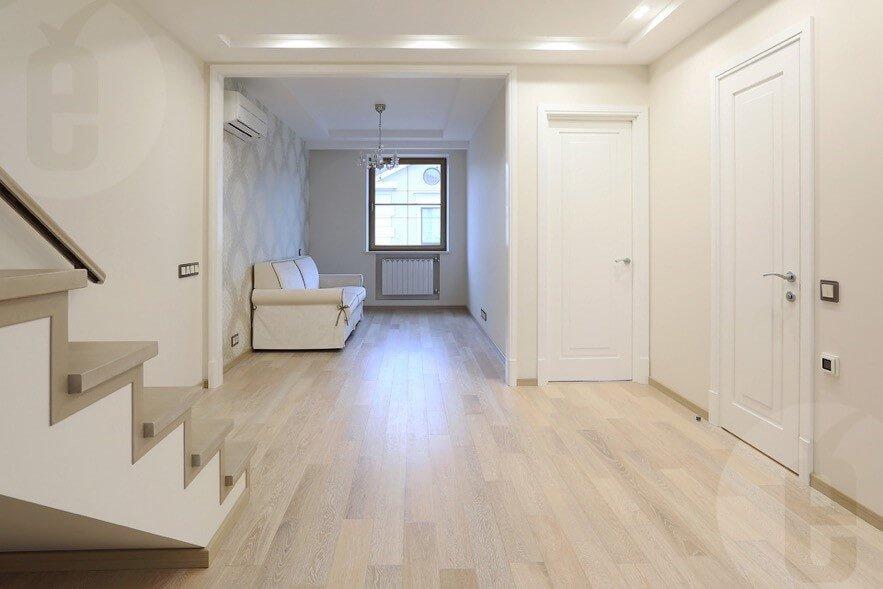 Первый этаж дома, где белые двери со светллым полом, а также лестница