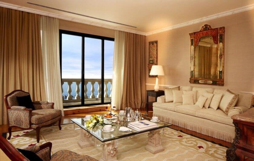 Панорамное остекление в сочетании с воздушным тюлем придает легкости и свежести бежевой гостиной