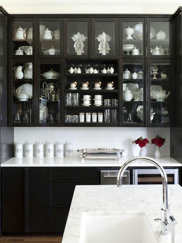 Беспроигрышное сочетание черного и белого отлично применяется на темной кухне в виде акцентного белого фартука и светлой посуды в стеклянных шкафчиках.
