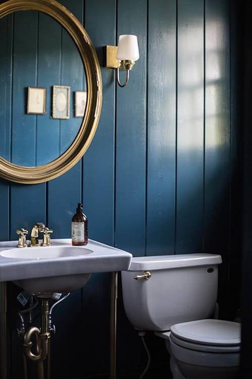 Обновить деревянную стену можно с помощью дымчатого оттенка с металическим свечением, который великолепно сочетается с латунными светильниками.