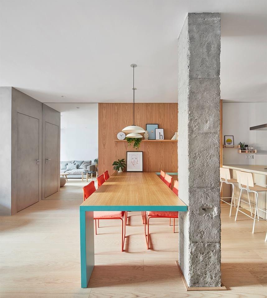 Стена, обшитая натуральным деревом светлого оттенка, эффектно контрастирует с грубой бетонной колонной