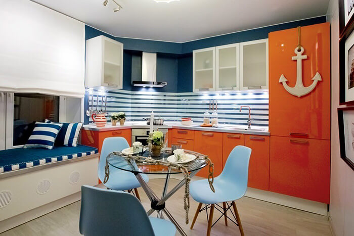 Оранжевые акценты на голубой кухне разбавляют холодность палитры и добавляют живого огонька в интерьер