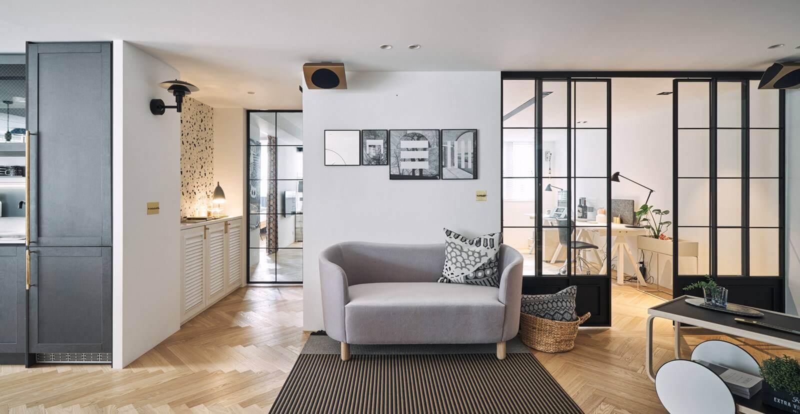 Кабинет отделен от гостиной с помощью раздвижной стеклянной системы, которая выполняет не только свою прямую функцию, но и является декоративным украшением помещения