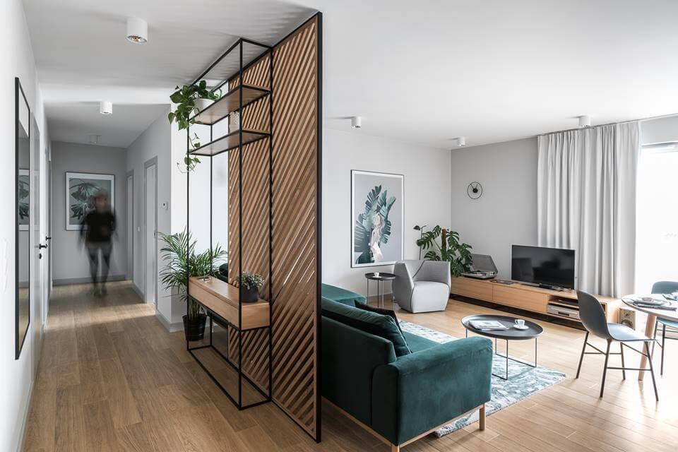 Интерьер гостиной построен на контрасте нейтральных оттенков серого и ярких глубоких цветовых акцентах насыщенного изумруда