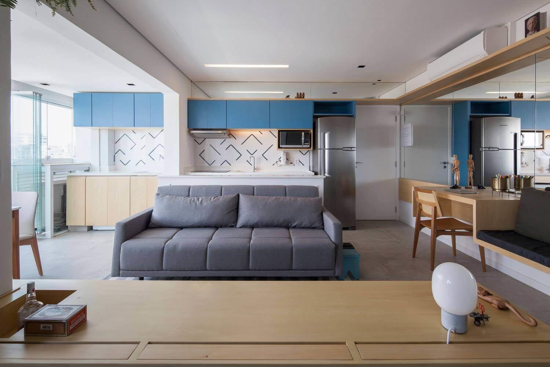 Для визуального расширения гостиной одна из стен является зеркальной