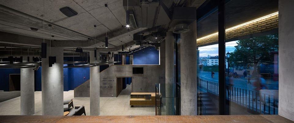 Фото вестибюля театра с серым бетонным потолком, бетонными колонами и панорамным остеклением