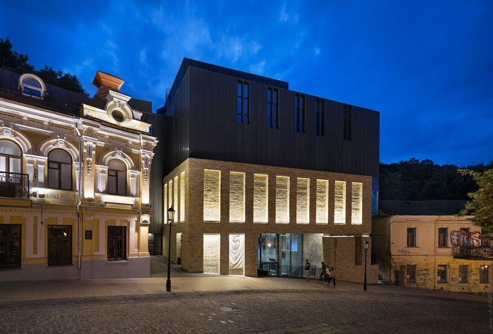 Фото фасада театра на Подоле. Фасад разделен на две части, где нижняя облицована желтым кирпичом, а верхняя – металлом