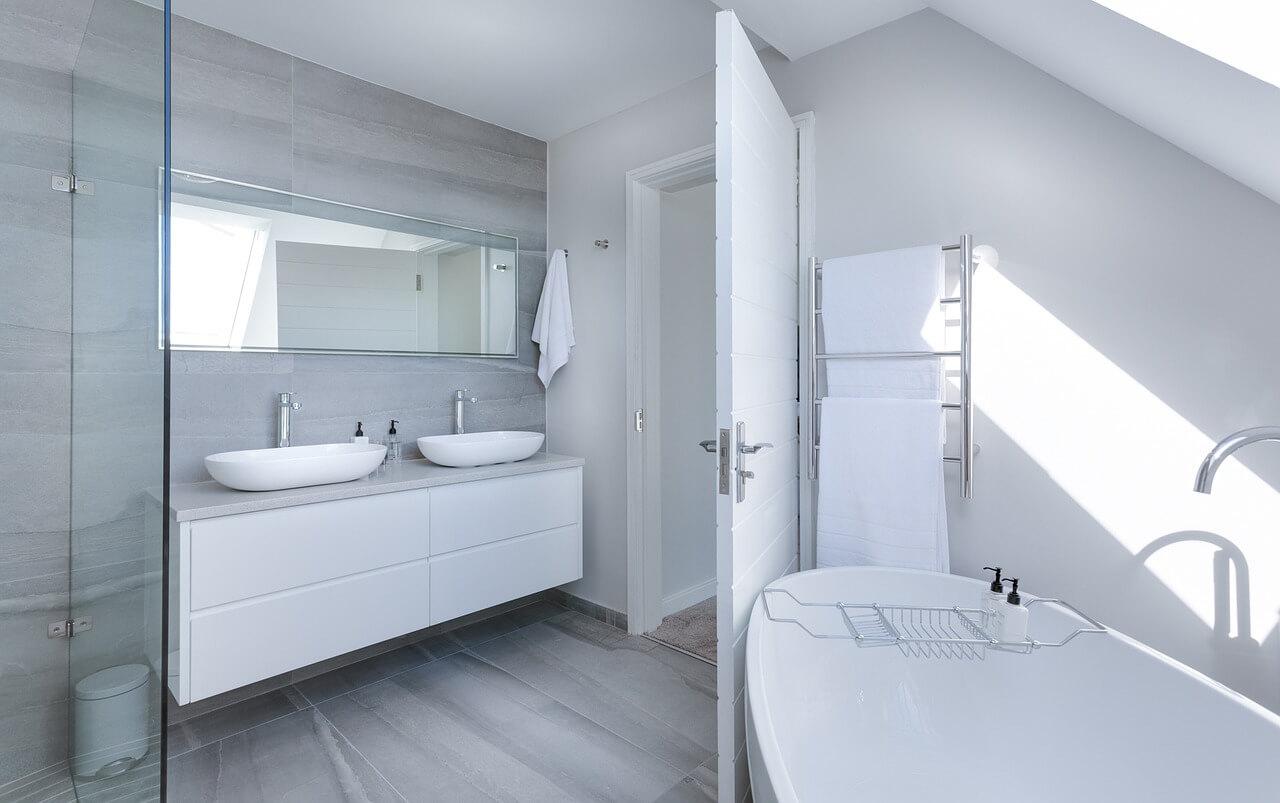 Минималистично оформленная ванная комната с душевым уголком за стеклянными стенками.
