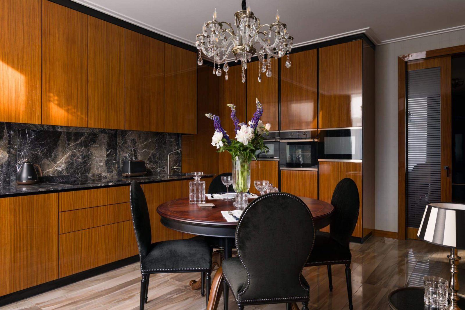 Кухня выглядит подчеркунто сдержанно, ведь вся кухонная техника«прячется» за гладкими деревянными панелями, создавая впечатление чистоты иизящества